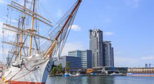Gdynia nad morzem Batyckim. Statek aglowy (3 - masztowa fregata) zacumowany przy Molo Poudniowym Portu w Gdyni. W gbi wida wiee drapacza chmur